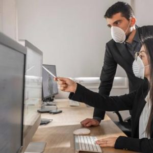 Two people wearing masks look at a computer monitor.